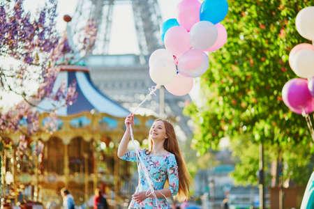 エッフェル塔とパリ、フランスでメリーゴーランドの前でピンクとブルーの風船の束を持つ幸せな少女