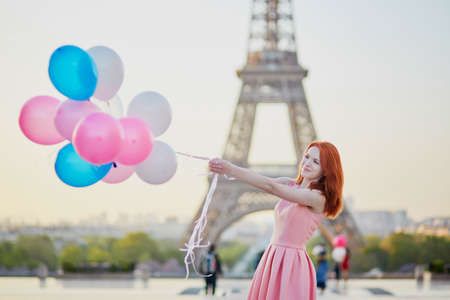 Happy young girl with bunch of pink and blue balloons in front of the Eiffel tower in Paris, France Imagens