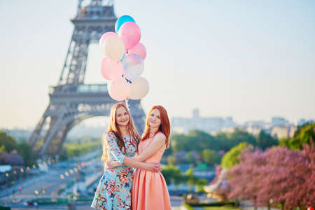 Two beautiful girls with bunch of pink and blue balloons in front of the Eiffel tower in Paris, France