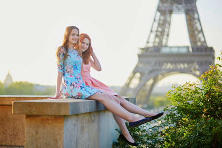 relatives: Two beautiful young girls near the Eiffel tower, enjoying their time in Paris, France Stock Photo