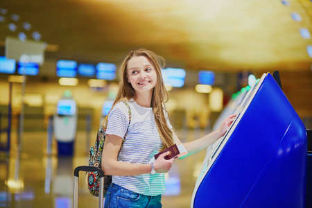 Beautiful young tourist girl with backpack and carry on luggage in international airport, doing self check-in