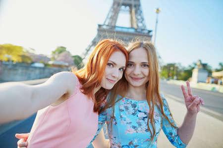 Two friends taking selfie near the Eiffel tower in Paris, France Imagens