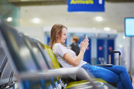 Young traveler with carry on luggage in international airport checking her mobile phone while waiting for her flight Фото со стока