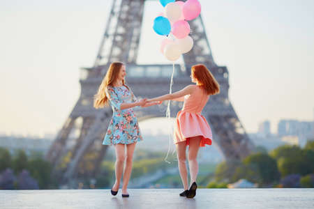 Two beautiful girls with bunch of pink and blue balloons dancing in front of the Eiffel tower in Paris, France Фото со стока