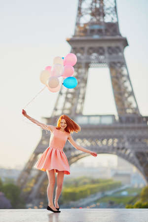 Happy young girl with bunch of pink and blue balloons in front of the Eiffel tower in Paris, France Stockfoto