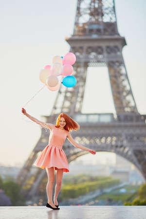 Gelukkig jong meisje met een bos van roze en blauwe ballonnen voor de Eiffeltoren in Parijs, Frankrijk