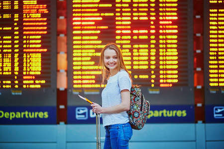Beautiful young tourist girl with backpack and carry on luggage in international airport, near flight information board Reklamní fotografie