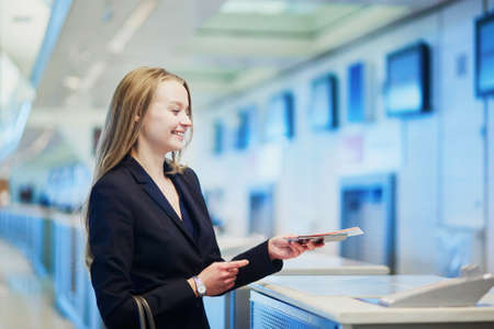 Young business woman in international airport at check-in counter, giving her passport to an officer and waiting for her boarding pass