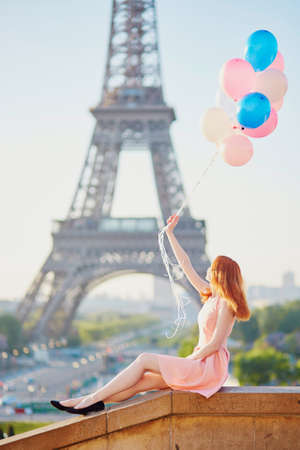 Happy young girl with bunch of pink and blue balloons in front of the Eiffel tower in Paris, France Stock fotó