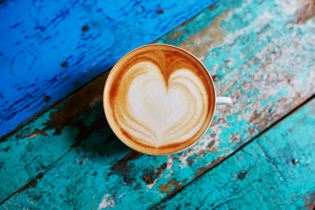 Cup of fresh coffee with heart form milk drawing on blue wooden table, view from above, flat lay