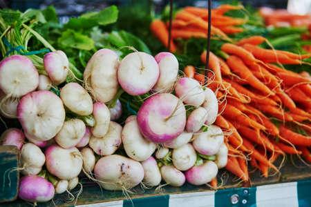 Large heap of fresh ripe organic turnips and carrots on farmer market in Paris, France