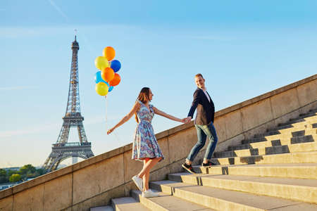 Loving couple with bunch of colorful balloons walking up the stairs near the Eiffel tower in Paris, France