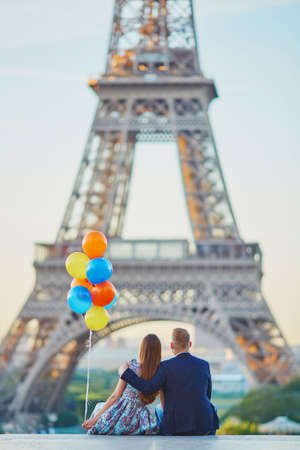 sweethearts: Loving couple with bunch of colorful balloons looking at the Eiffel tower in Paris, France