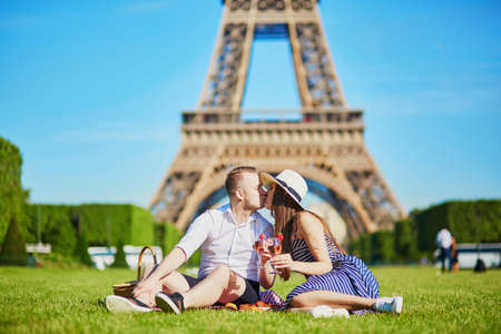 Romantic couple having picnic near the Eiffel tower in Paris, France Stock Photo