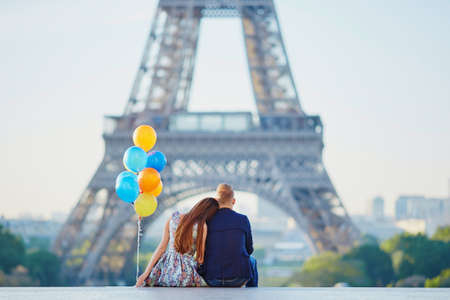Loving couple with bunch of colorful balloons looking at the Eiffel tower in Paris, France