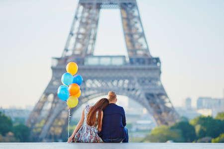 Liefdevolle paar met een heleboel kleurrijke ballonnen die naar de Eiffeltoren in Parijs, Frankrijk kijken