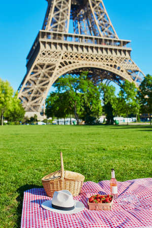 Beautiful picnic set with basket, pink wine, strawberries and glasses on the grass near the Eiffel tower, Paris, France Stock fotó
