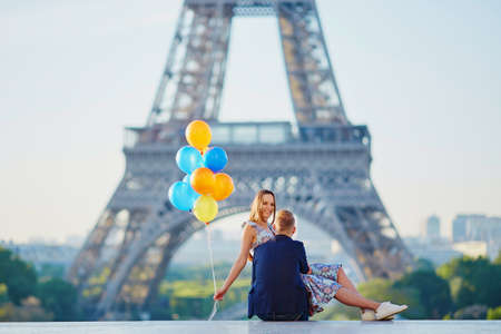 sweethearts: Loving couple with bunch of colorful balloons near the Eiffel tower in Paris, France