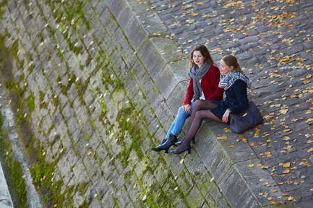 Two young girls walking together near the river Seine in Paris on a sunny fall day. Tourism or friendship concept