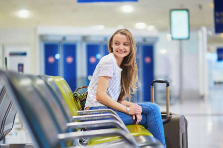 Beautiful young tourist girl with backpack and carry on luggage in international airport, waiting for flight