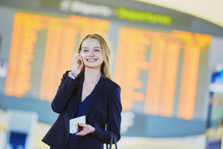 Young elegant business woman holding passport and boarding pass, talking on the mobile phone near flight information board in international airport terminal