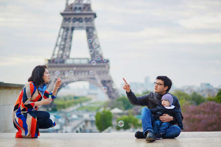 Happy family of three in Paris near the Eiffel tower. Mother, father and little son playing with bubbles and enjoying their vacation in France