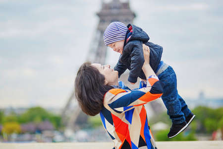 Mother throwing her little son in the air near the Eiffel tower in Paris. Happy family of two enjoying their vacation in France. Imagens