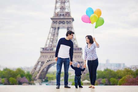 パリのエッフェル塔の近くの色とりどりの風船の束を持つ 3 つの幸せな家族。母親、父親と幼い息子のフランスでの休暇を楽しんで