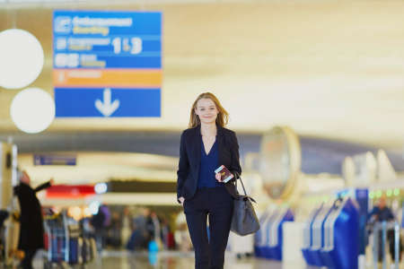 Young elegant business woman with hand luggage walking through the international airport terminal. Cabin crew member with suitcase Stock fotó - 81409989