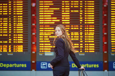 Young elegant business woman with hand luggage in international airport terminal, looking at information board, checking her flight. Cabin crew member with suitcase. Reklamní fotografie