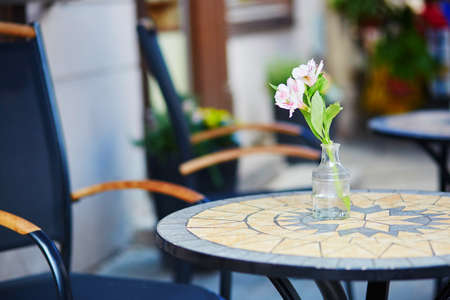 Table of an outdoor cafe in Vilnius, Lithuania, decorated with flower on a summer day Reklamní fotografie - 82020686