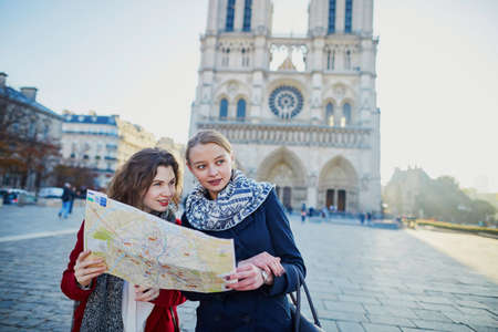 2 人の少女は、パリのノートルダム大聖堂の近くの地図を一緒に歩きます。観光や友情の概念 写真素材
