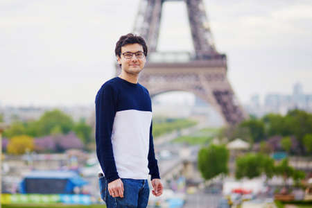Handsome man in Paris in front of the Eiffel tower