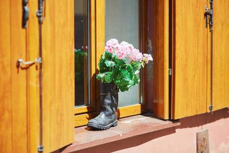 窓枠に高いブーツのピンクの花