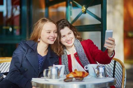 2 つ若い女の子パリの屋外カフェでクロワッサンと携帯電話を使用する selfie とコーヒーを飲みます。友情の概念