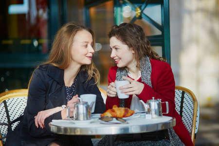 2 つ若い女の子パリの屋外カフェでクロワッサンとチャットでコーヒーを飲みます。友情の概念