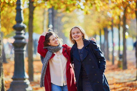 Two young girls walking in autumn park on sunny fall day. Friendship concept