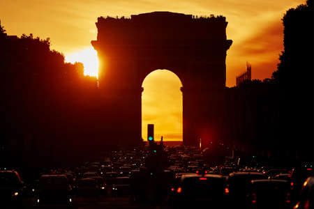 Traffic jam with lots of vehices in Paris on Champs-Elysees street with Triumphal Arch and dramatic sunset on a hot summer day