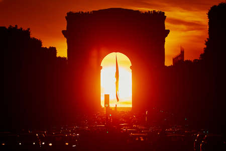 Traffic jam with lots of vehices in Paris on Champs-Elysees street with Triumphal Arch and dramatic sunset on a hot summer day, sun is right in the middle of the arch