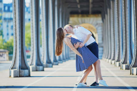 Romantic couple kissing on Bir-Hakeim bridge in Paris, France