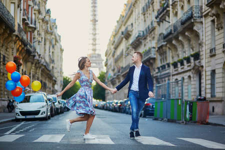 Romantic couple running across the street with Eiffel tower in background in Paris, France