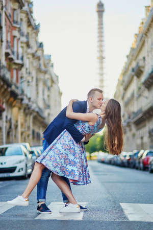 Romantic couple kissing on the street with Eiffel tower in background in Paris, France