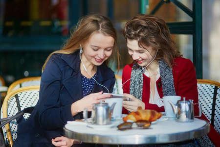 2 つ若い女の子パリの屋外カフェでクロワッサンとコーヒーを飲むと、イヤホンを使用して音楽を聴きます。友情の概念