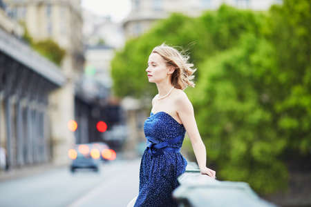 Beautiful young elegant French woman in Paris outdoors
