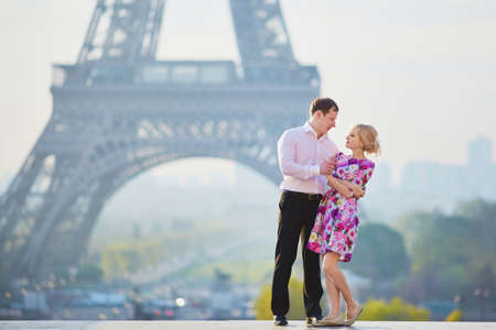 Beautiful romantic couple hugging in front of the Eiffel tower in Paris, France Stock Photo