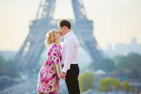 Beautiful romantic couple kissing in front of the Eiffel tower in Paris, France