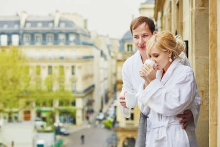 Happy young couple in white bathrobes drinking coffee together on balcony with view to Paris, France. Hotel, travel, relationships, and happiness concept Stock Photo
