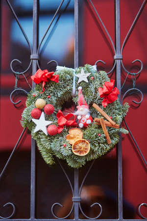 Beautiful Christmas wreath with dry fruits and toys in French or German town
