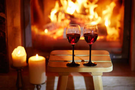 Two glasses of red wine near fireplace with many candles. Cozy romantic evening for couple or Christmas celebration concept Stock Photo