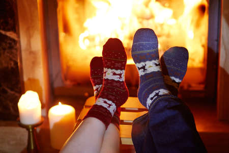 Man and woman in warm socks near fireplace. Cozy romantic evening for two or Christmas celebration concept